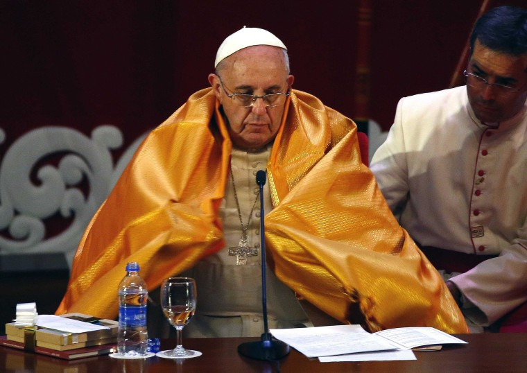 Image: Pope Francis wears a saffron-coloured robe as he attends the Interreligious Encounter at the Bmich in Colombo