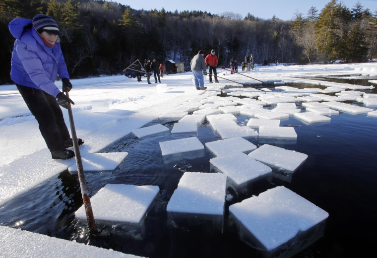 Image: Jane Kellogg, left, works to guide ice blocks weighing 120 to 160 pounds during the annual ice harvest on Squam Lake