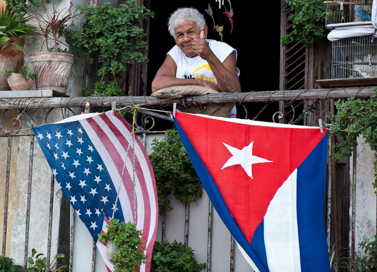Image: A Cuban gives the thumbs up from his balcony decorated with the US and Cuban flags  in Havana