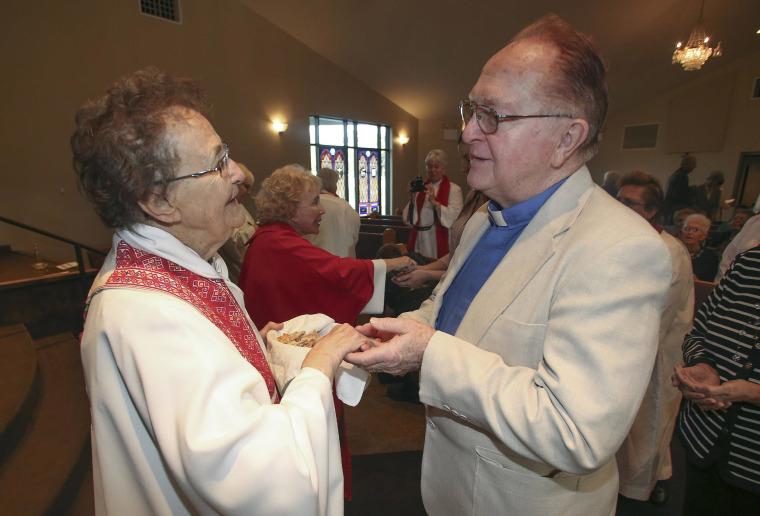 Image: Rita Lucey, left,  performs communion for Episcopalian Father Jim Coleman