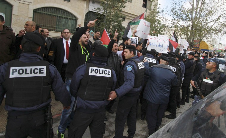 Image: Palestinian policemen hold back demonstrators protesting against Canadian Foreign Minister John Baird, as Baird meets with his Palestinian counterpart in the West Bank city of Ramallah