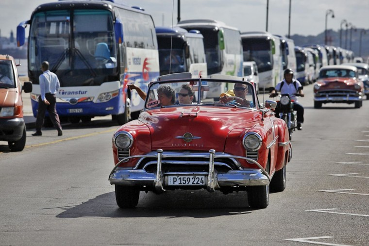 Tourists ride in a taxi in Havana. Despite the existence of modern transportation, tourists still prefer vintage automobiles.