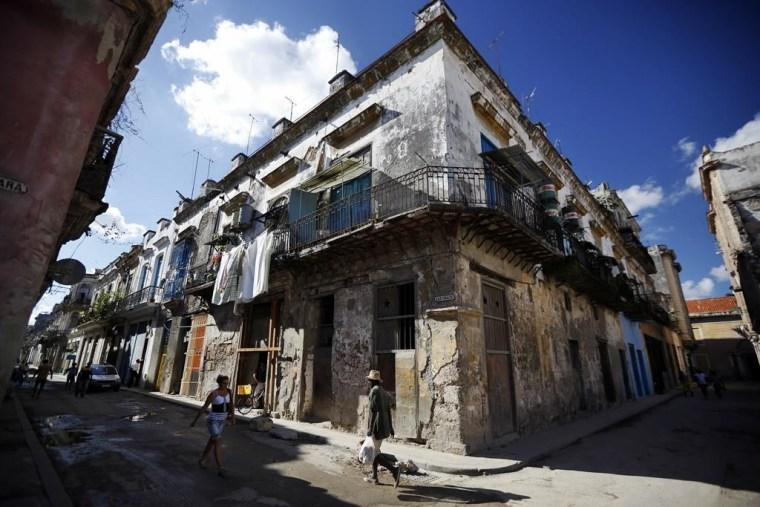 Pedestrians pass crumbling buildings in Old Havana.