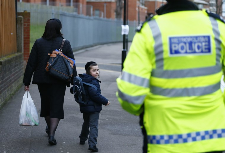 Image: A young member of the Jewish community looks back at a police officer in north London