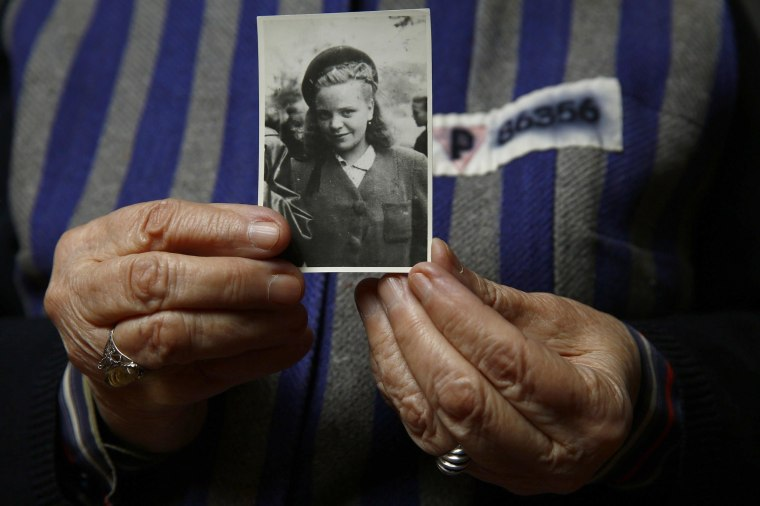 Image: Auschwitz death camp survivor Jadwiga Bogucka holds a picture of herself from 1944 in Warsaw