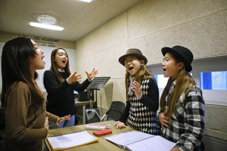 Kim Si-yoon (2nd R) and Yoo Ga-eul (R) take part in a singing lesson at DEF Dance Skool in Seoul November 15, 2014.