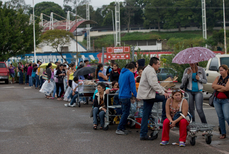 Patrons line up on a supermarket parking lot in San Cristobal, Venezuela, Thursday, Jan. 22, 2015. The combination of shortages and spiraling inflation have shaken support for President Nicolas Maduro even among the poor who rely on the social programs launched by his mentor, the late President Hugo Chavez. (AP Photo/Fernando Llano)