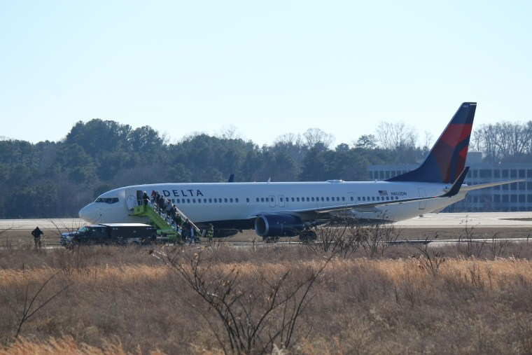 Passengers are evacuated from Delta Flight Flight 1156 at Hartsfield-Jackson International Airport after a a bomb threat on Jan. 24.