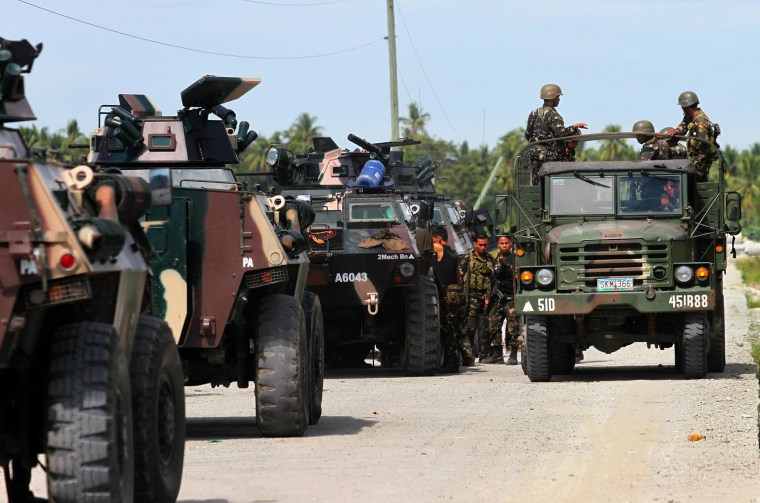 Image: Military personnel ride on a truck past APCs in the town of Mamasapano in the Philippines on Monday