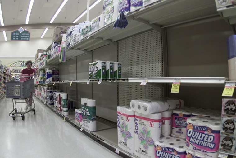 A shopper passes by a nearly empty toilet paper shelf.