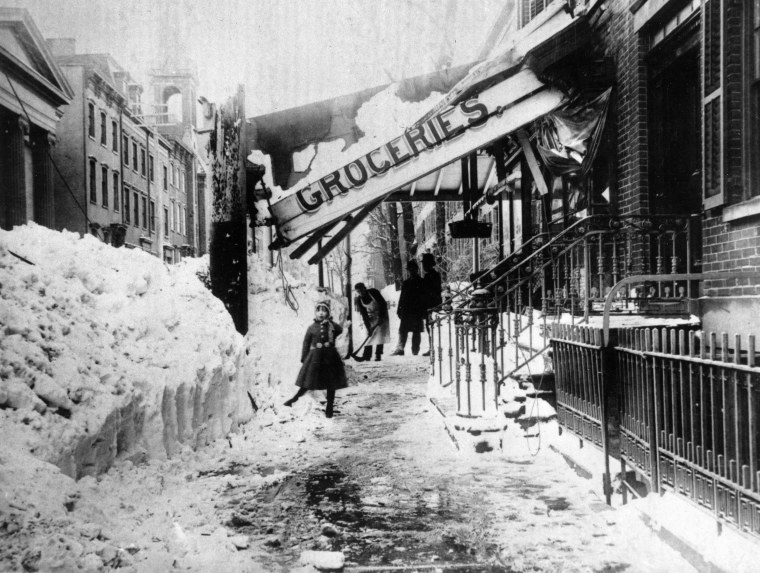 The awning of a grocery store is damaged from the weight of the snow during the blizzard of 1888 in New York City.