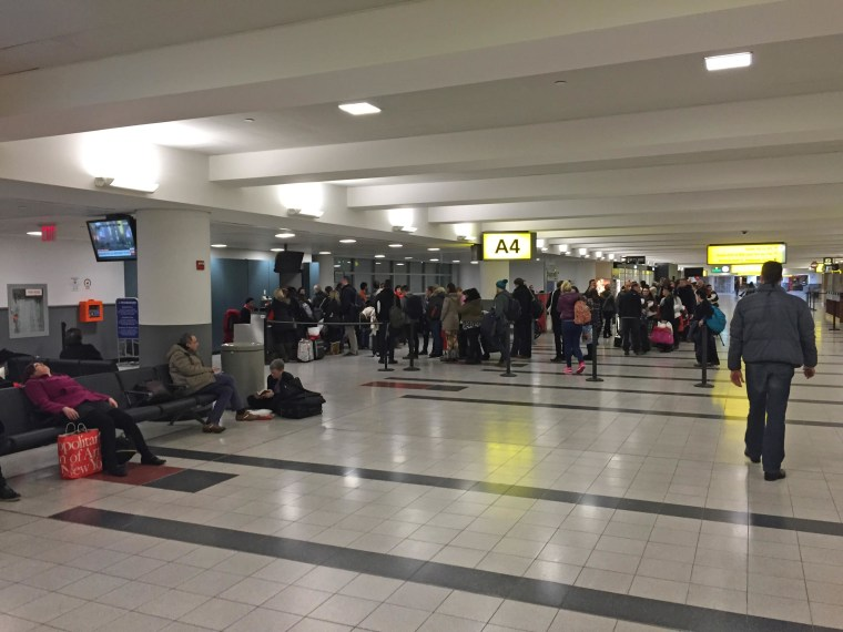 Travelers wait at JFK airport early Tuesday, Jan. 27 after a Virgin Atlantic flight was cancelled after six hours on the tarmac.