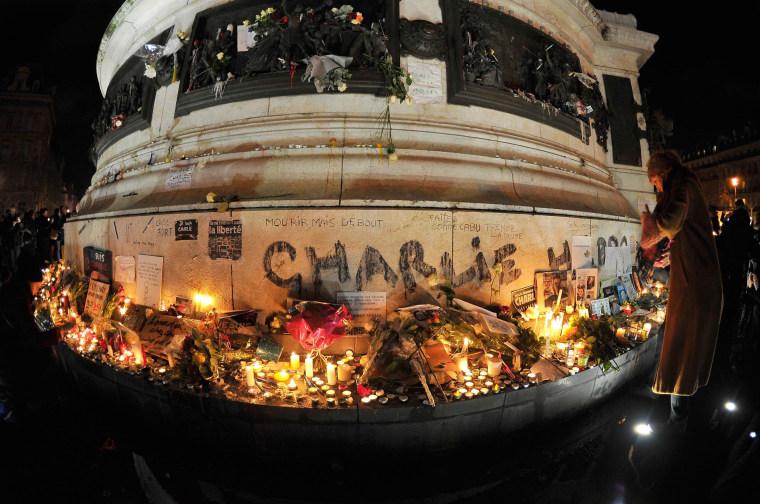Image: People gather to light candles at Place de la Republique