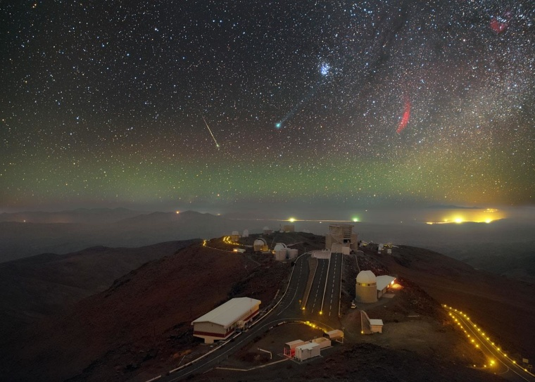 Glowing green, Comet Lovejoy takes center stage in a celestial scene at the European Southern Observatory at La Silla, Chile. Other players on the stage include the Pleiades, above and to the right of the comet; the California Nebula, appearing in the form of a red arc of gas directly to Lovejoy's right; and a meteor streaking downward to Lovejoy's left. The telescopes of La Silla provide an audience for this celestial performance, and a thin shroud of low-altitude cloud clings to the plain below the observatory streaked by the Panamericana Highway. This composite image was taken by ESO Photo Ambassador Petr Horalek during a visit to La Silla in January 2015.
