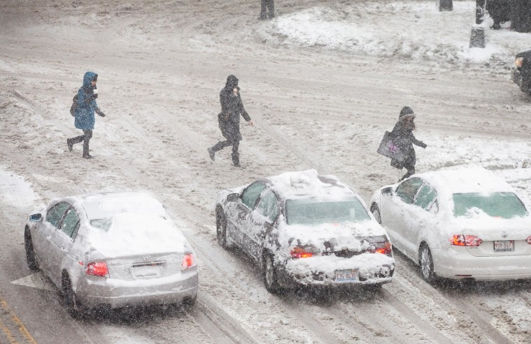 Image: Pedestrian and motorists navigate a snow-covered street in Chicago