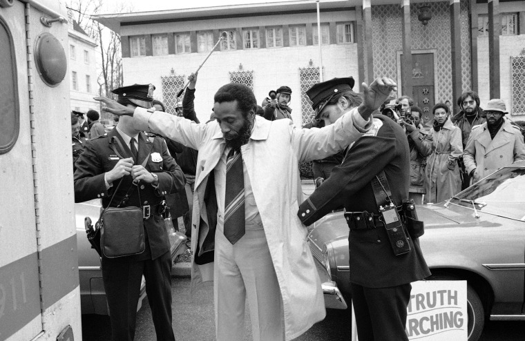 A policeman frisks human rights activist Dick Gregory following his arrest while picketing the South African embassy in Washington, Dec. 25, 1977. Gregory, and wife Lillian, were charged with demonstrating within 500 feet of an embassy. The two, along with a handful of supporters were protesting the South African regime's treatment of blacks.