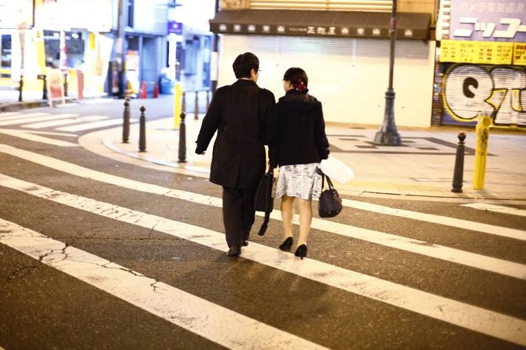 Image: Couple cross street in amusement district of Osaka