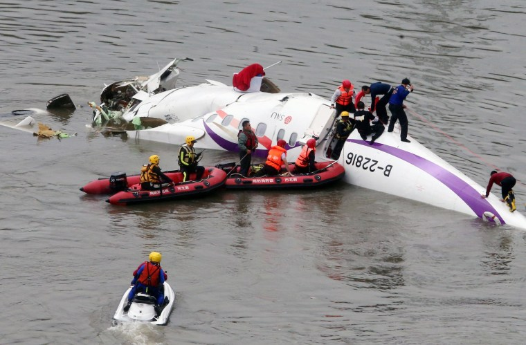 Image: Emergency personnel approach a commercial plane after it crashed in Taipei