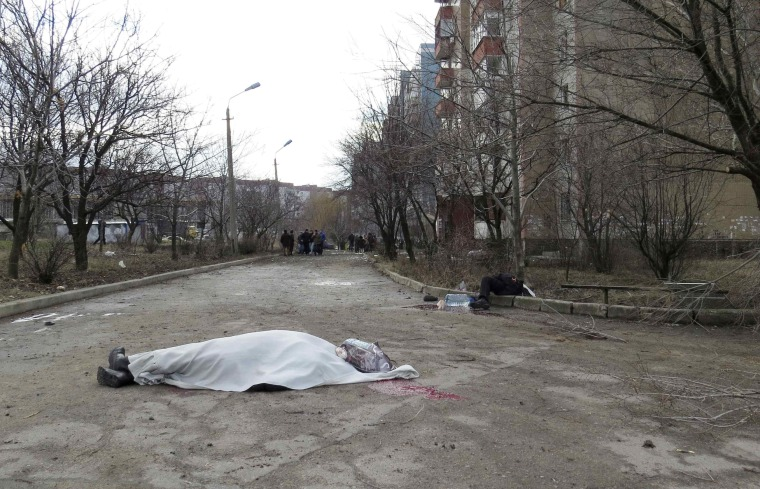 Image: The covered bodies of victims are seen outside a building neighbouring a hospital in Donetsk
