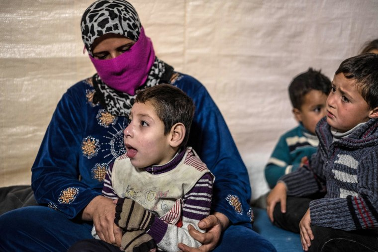 Um Ali holds her oldest son Ali, 7, who suffered brain damage at birth in Lebanon's Bekaa Valley. Ali is paralyzed and cannot speak. Um Ali says Ali will needs surgery to straighten his spine, but there is no medical support available. Ali's brothers Hassan and Hussein are at right.