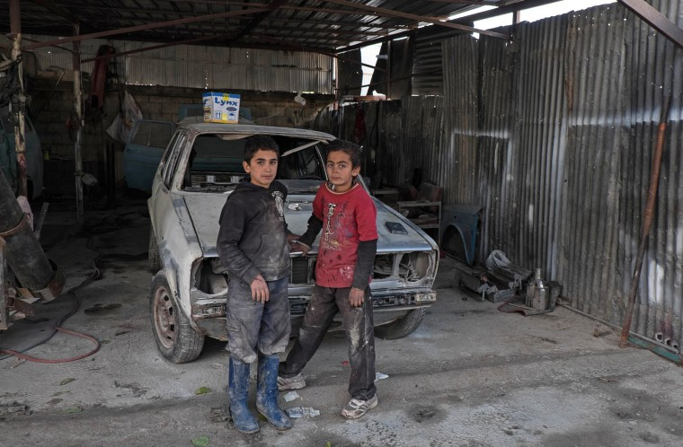 From left, Syrian refugees Mahmoud, 12, and Hussein, 8, work in an auto garage sanding down and welding old cars 12 hours a day in Lebanon's Bekaa Valley.