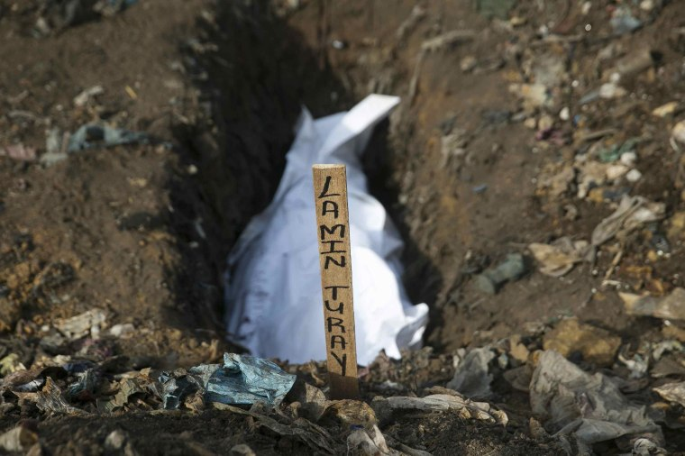 Image: The body of a suspected Ebola victim awaits burial in a grave at a cemetery in Freetown