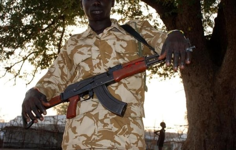 """David"", 15, stands holding an assault rifle on January 27, two days before his release from the SSDA Cobra Faction armed group, in Jonglei State, South Sudan."
