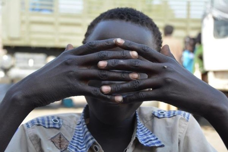 A South Sudanese child soldier hides his face with his hands.