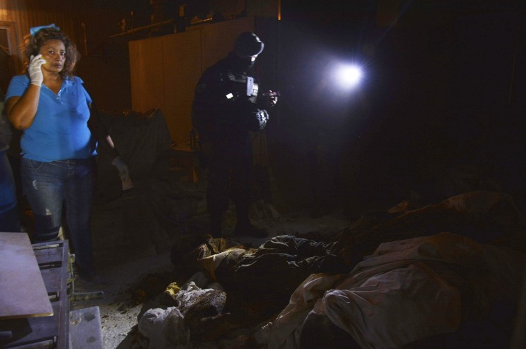 epa04605647 Policemen and forensic experts look for evidence inside a disused crematorium where a total 61 bodies were found in Acapulco, state of Guerrero, Mexico, 06 January 2015. The bodies were discovered after a resident's call to the authorities.  EPA/FRANCISCO MEZA