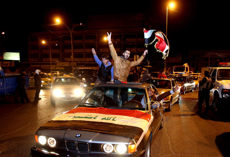 Image: Iraqis celebrate after the lifting of the night-time curfew