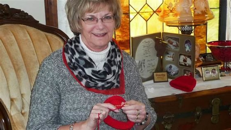 Sue Hipple knitting red caps for heart health awareness.