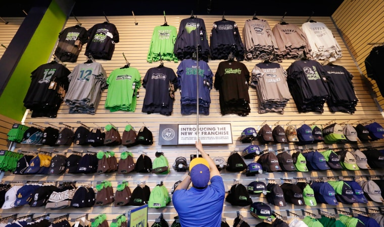 Image: Store manager Kevin Mak moves Seattle Seahawks' shirts