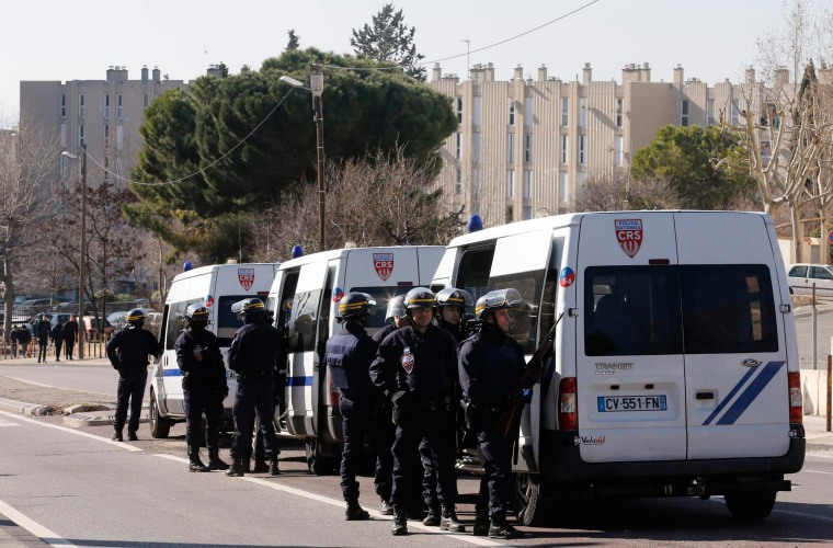 Image: French CRS riot police officers secure the access to the Castellane housing area in Marseille