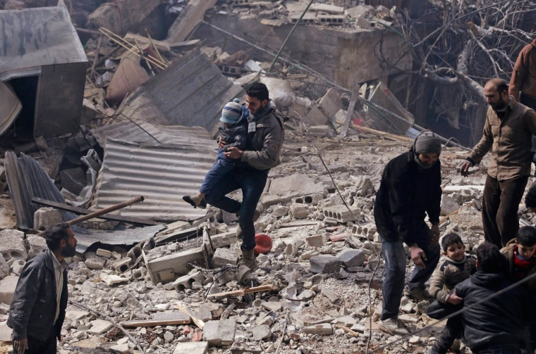 Image: Men carry children rescued from an area hit by airstrikes from forces loyal to Syria's President Assad in Damascus