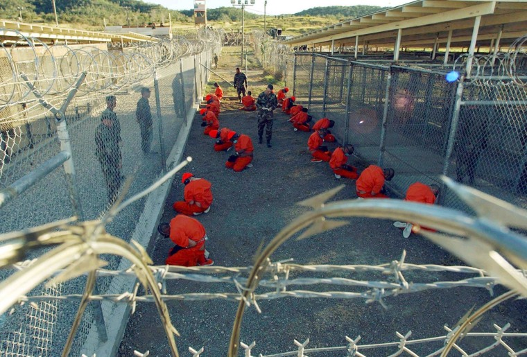 Image: Detainees in orange jumpsuits sit in a holding area at Naval Base Guantanamo Bay
