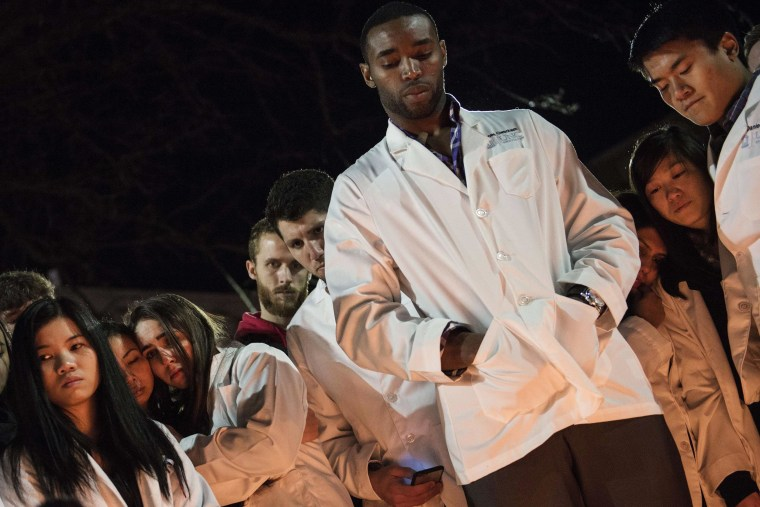 Image: Dentistry students and others huddle together during a vigil
