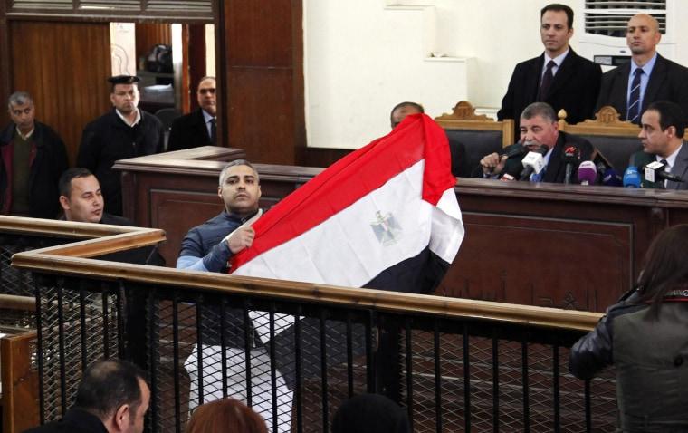 Image: Al Jazeera journalist Mohamed Fahmy raises Egyptian flag in court on Thursday