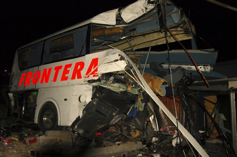 Image: The wreckage of a passenger bus is seen at the site of an accident in Anahuac