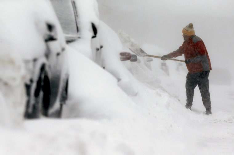 Image:man shovels snow in the East Boston