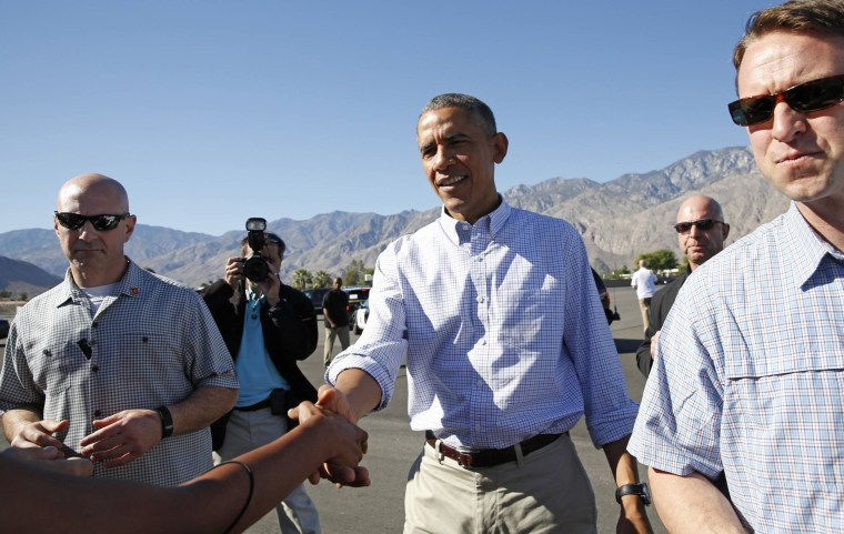 Image: U.S. President Obama extends his hand to greet a well-wisher upon his arrival in Palm Springs