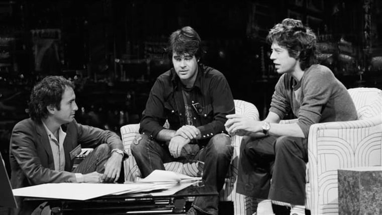 "Lorne Michaels in 1978 with cast member Dan Aykroyd and guest Mick Jagger, rehearsing a skit on the ""SNL"" set."
