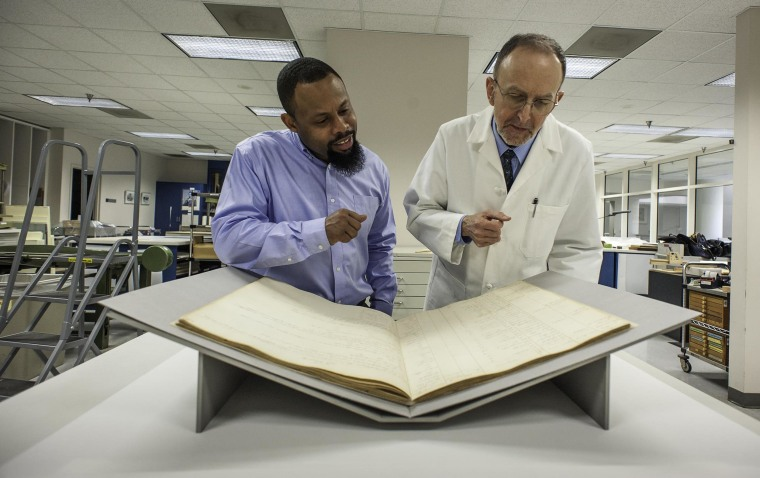 Image: At the National Arhives, Damani Davis, Reference Archivist and Steven Loew, Conservator, discuss the conservation and historical significane of the Book of Negroes.
