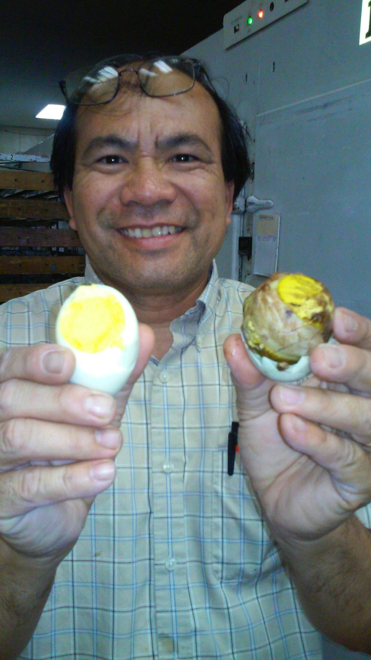 Thomas Chin Dam shows the difference between a fresh and a fertilized duck egg.