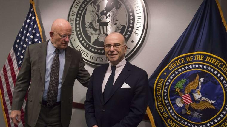 Image: US Director of National Intelligence James Clapper (L) greets French Interior Minister Bernard Cazeneuve