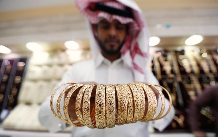 Image: A Saudi jeweller shows a customer gold bangles at a shop in Riyadh