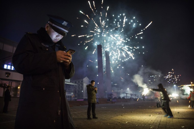 BEIJING, CHINA - February 19: A Chinese security guard checks his smartphone as fireworks explode during celebrations of the Lunar New Year early on February 19, 2015 in Beijing, China.The Chinese Lunar New Year of Sheep also known as the Spring Festival, which is based on the Lunisolar Chinese calendar, is celebrated from the first day of the first month of the lunar year and ends with Lantern Festival on the Fifteenth day. (Photo by Kevin Frayer/Getty Images)