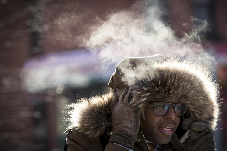 Image: A man talks on his phone while walking in the cold in Brooklyn borough of New York