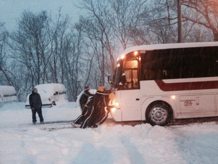 Image: The St. Marys College of Maryland men's basketball team pushes their bus out of the snow.