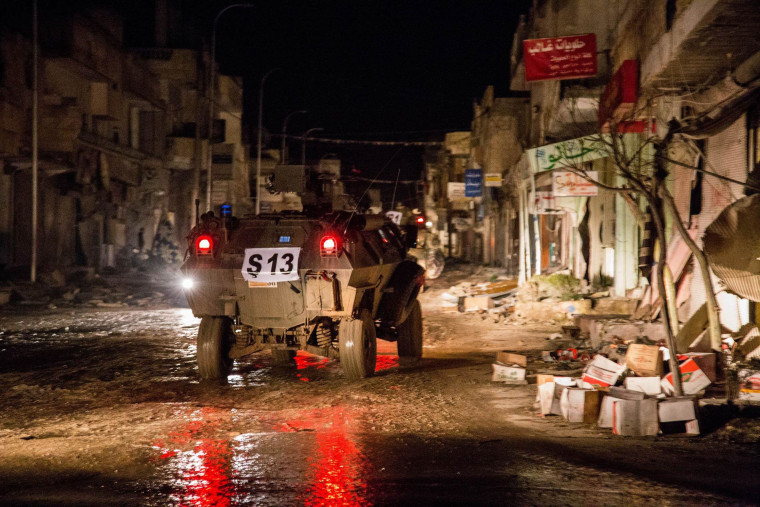 Image: Turkish army vehicles drive in a street of the Syrian town of Kobane.