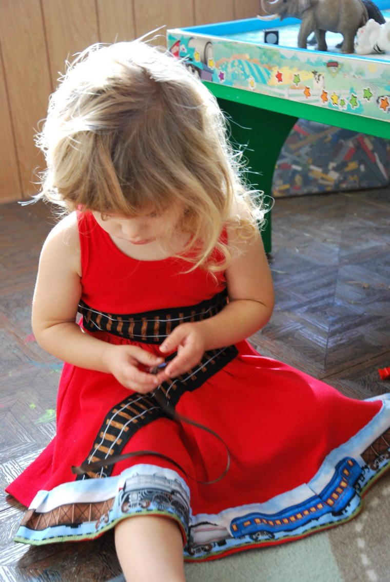 Model Sienna plays with her train-themed dress.